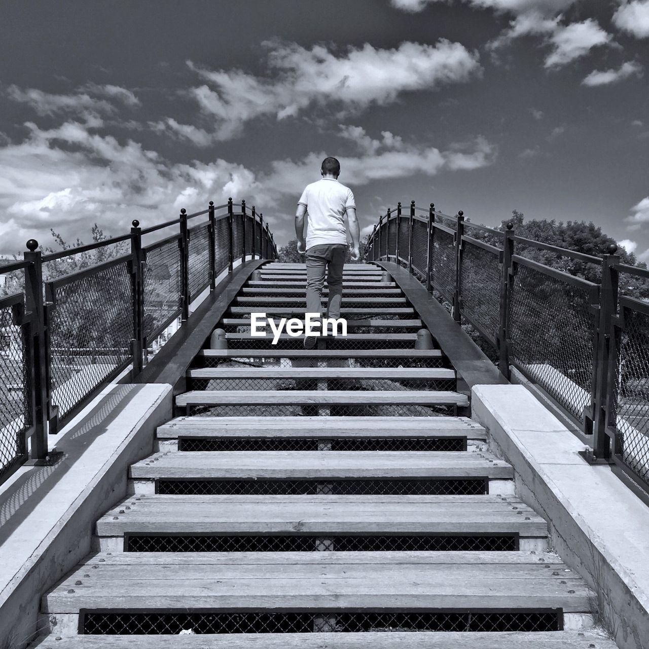 Rear view of man walking on steps of bridge against sky