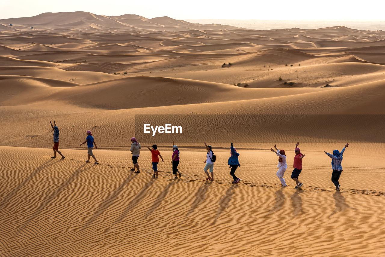 PEOPLE ON SAND DUNE