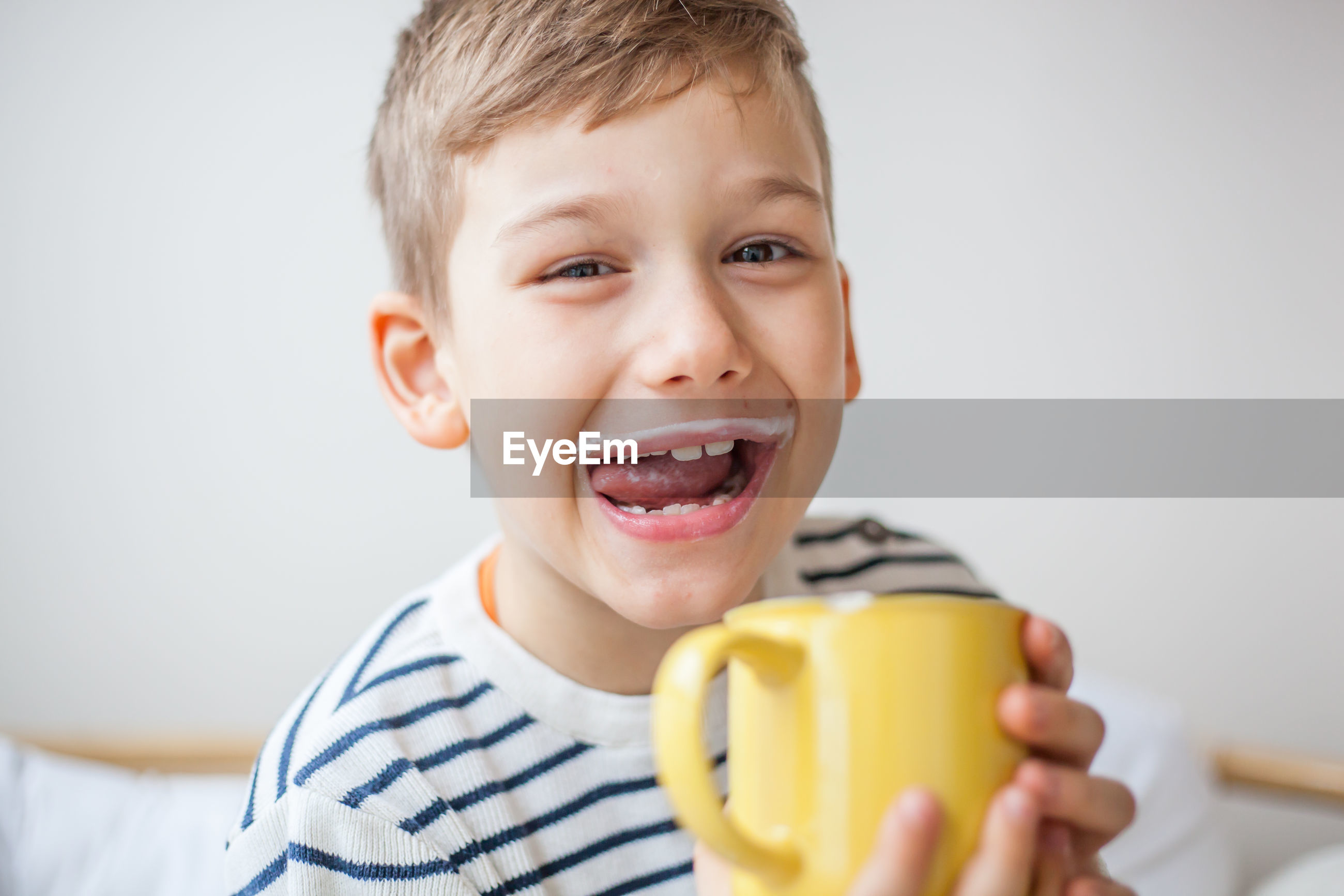 Portrait of smiling boy holding cup against wall