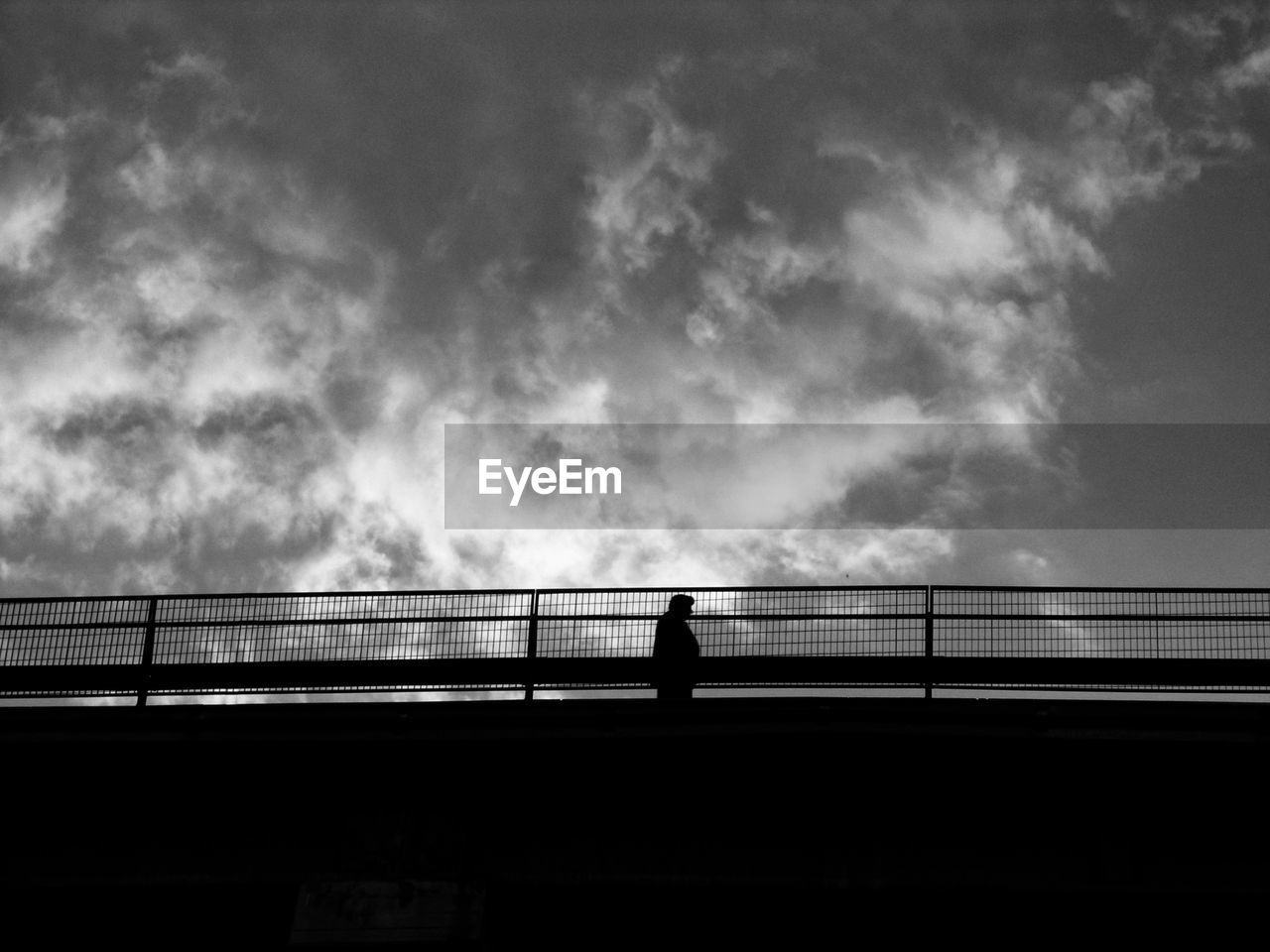 cloud - sky, sky, railing, silhouette, one person, connection, transportation, bridge, architecture, nature, built structure, real people, lifestyles, bridge - man made structure, standing, outdoors, men, walking