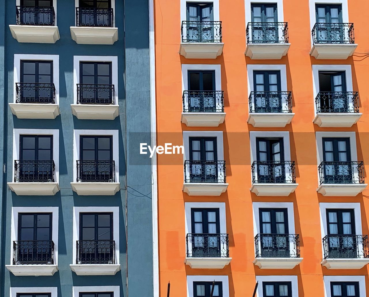 window, building exterior, built structure, full frame, architecture, building, residential district, backgrounds, no people, day, side by side, orange color, outdoors, glass - material, city, sunlight, in a row, low angle view, balcony, pattern, apartment, row house