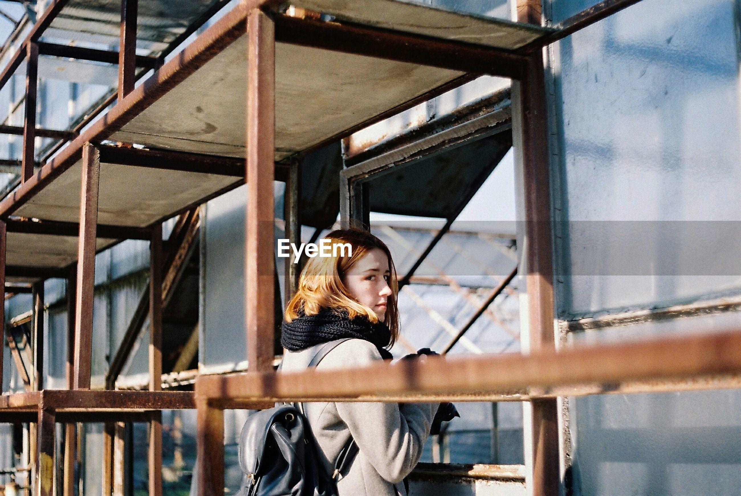 Woman standing under scaffolding
