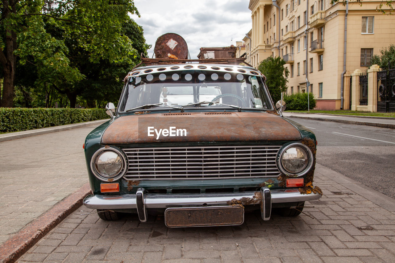 mode of transportation, transportation, retro styled, vintage car, architecture, building exterior, city, motor vehicle, land vehicle, car, day, tree, street, old, headlight, built structure, rusty, plant, metal, no people
