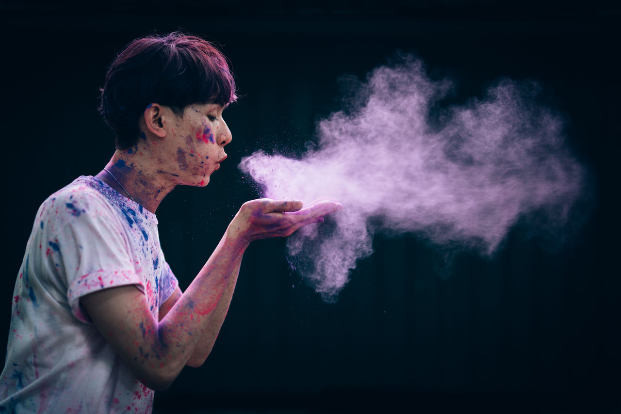 Side view of young man blowing powder paint against black background