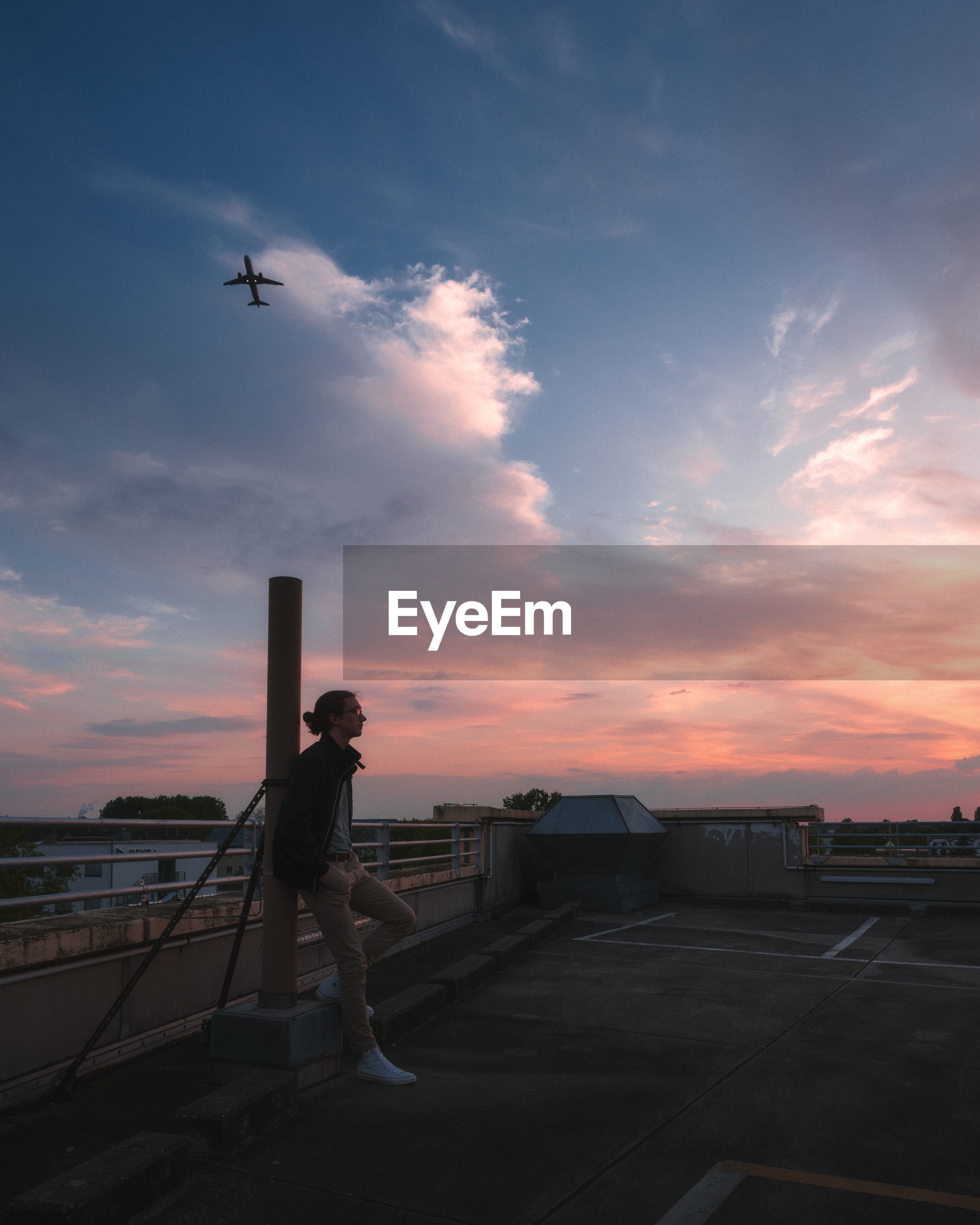 Teenage boy standing on terrace against sky during sunset