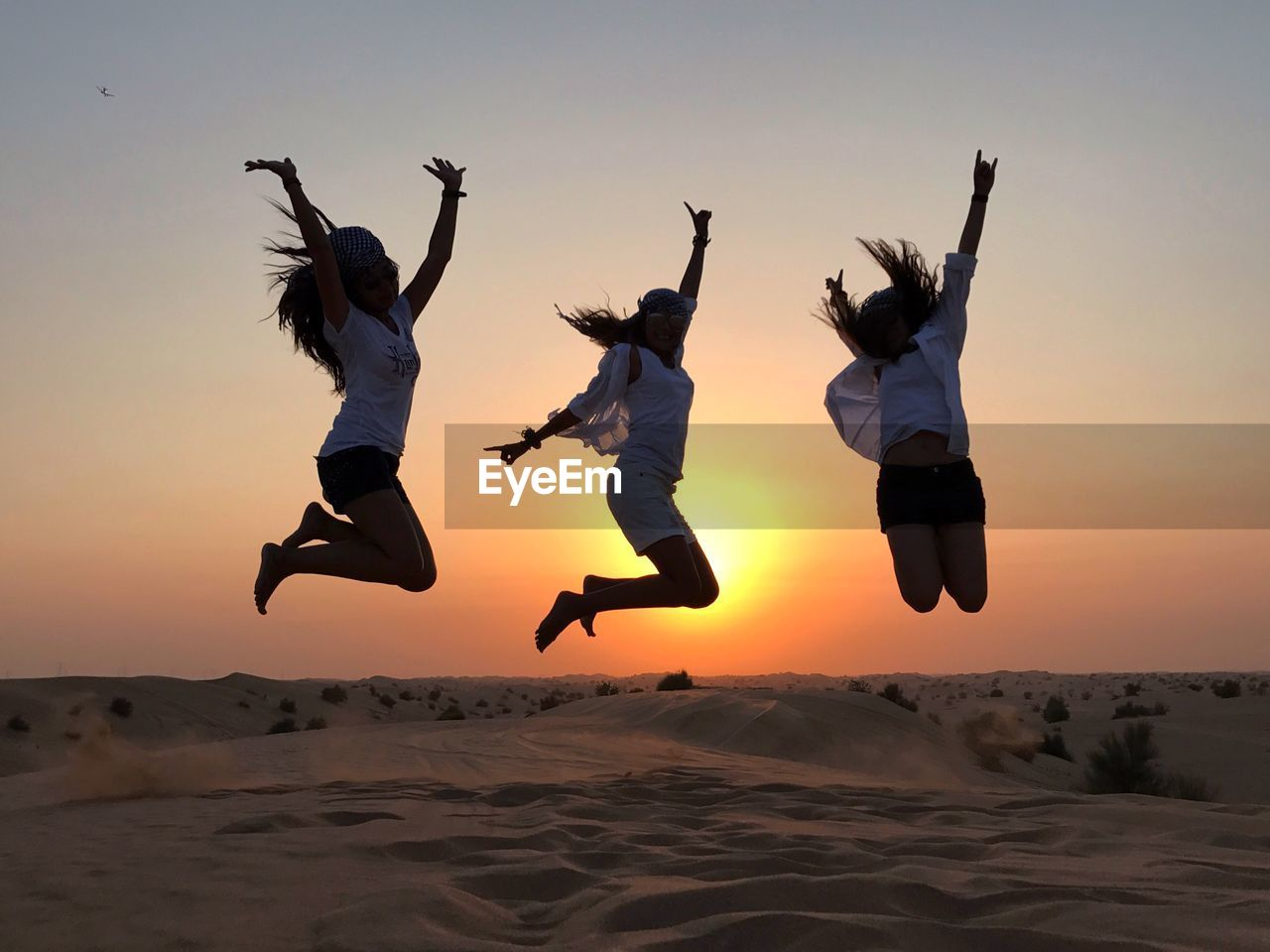 Happy friends jumping on sand against sky during sunset