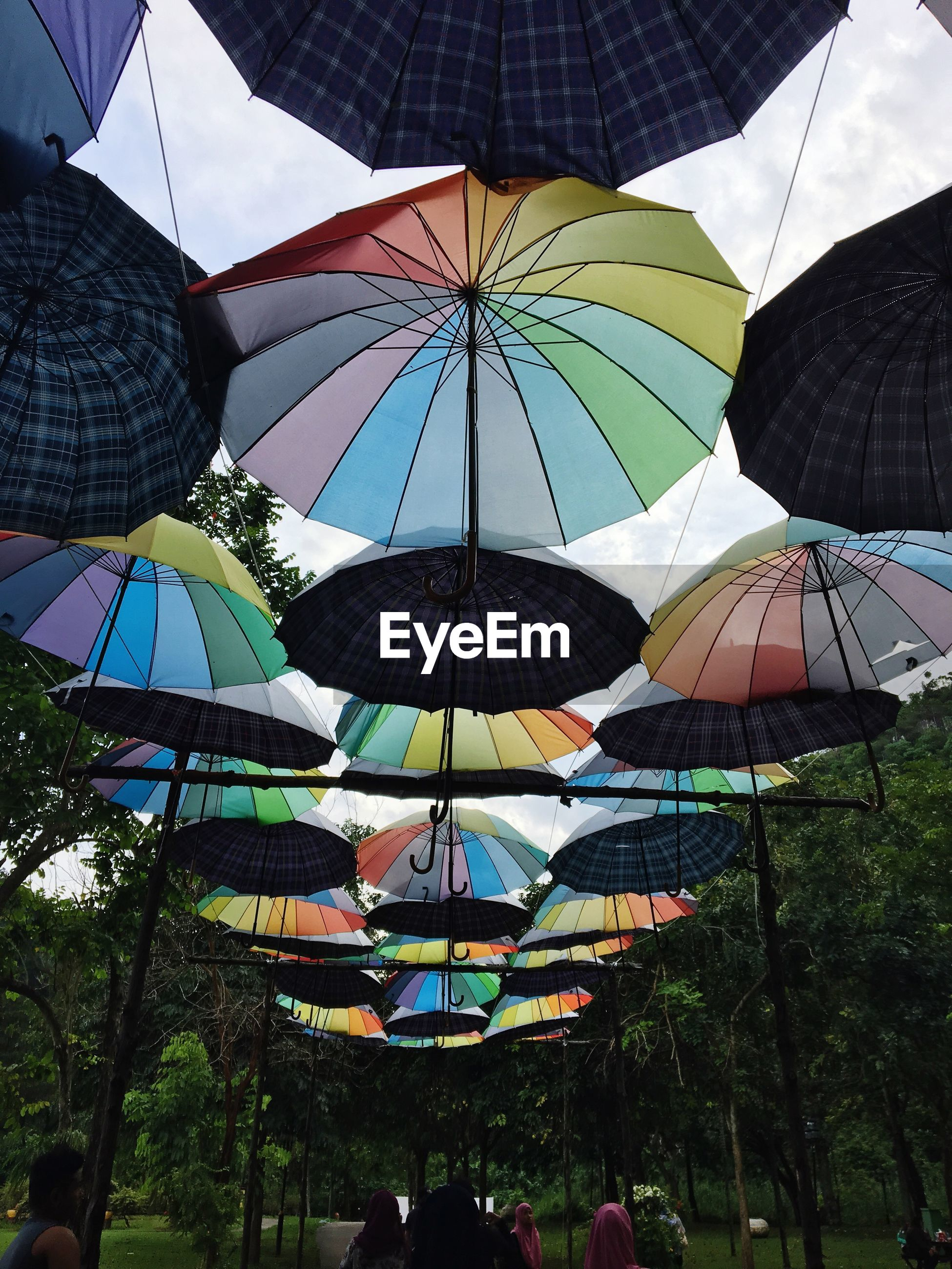 umbrella, protection, multi colored, low angle view, sky, cloud - sky, hanging, outdoors, no people, day