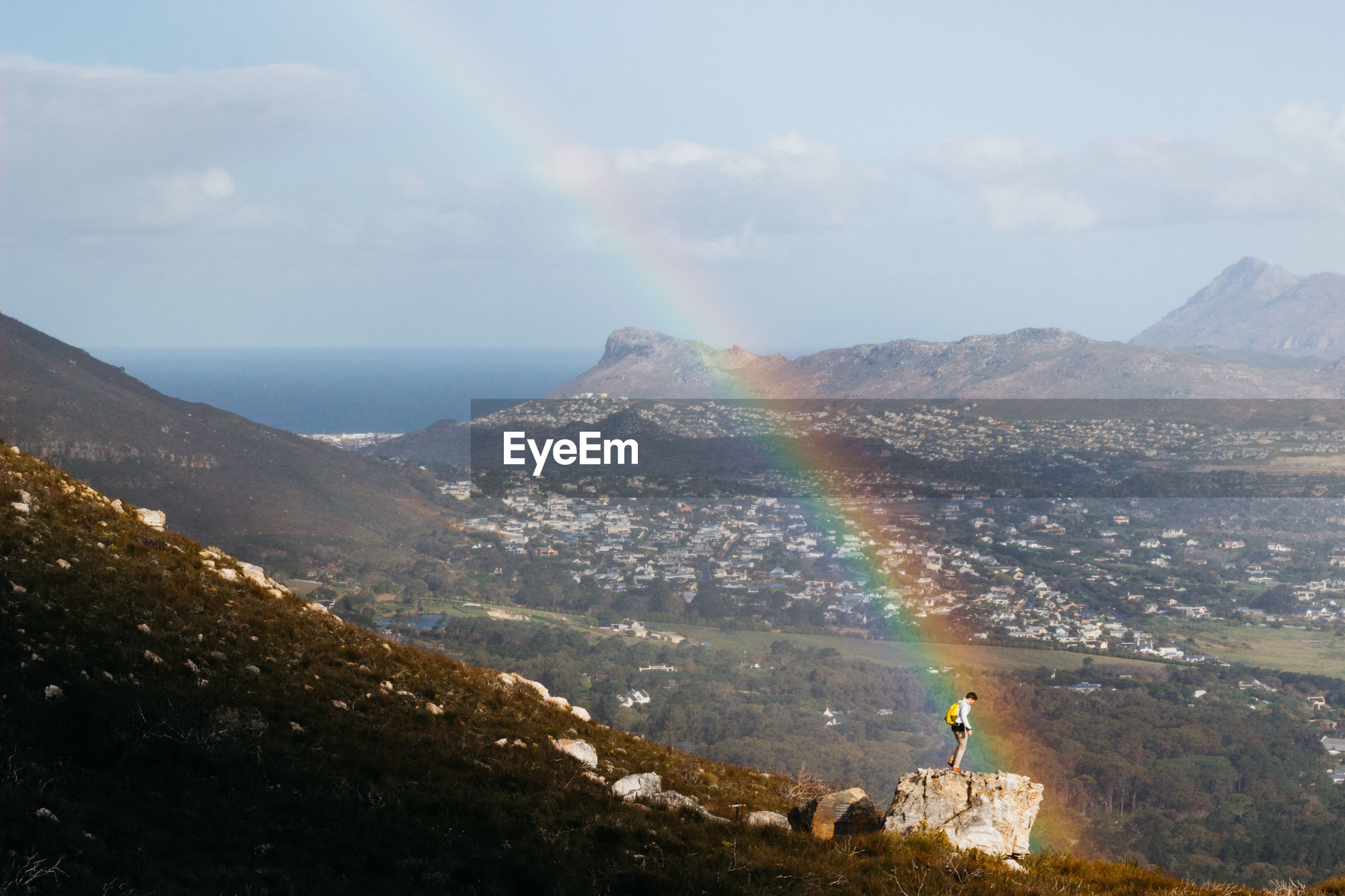 Man standing on mountain by rainbow against landscape
