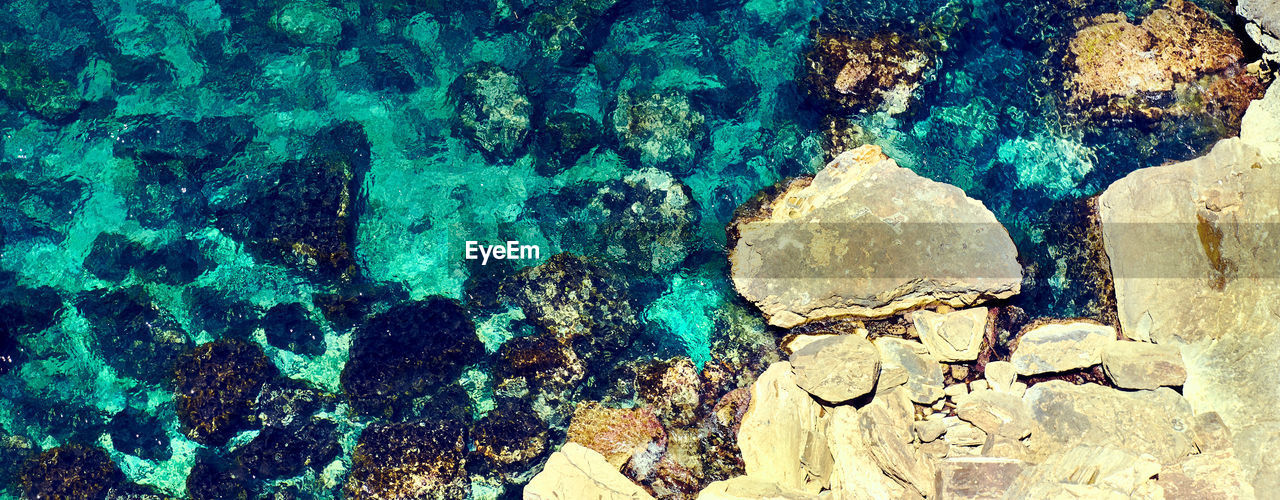 no people, water, rock, textured, solid, rock - object, day, full frame, backgrounds, nature, blue, pattern, outdoors, architecture, wall - building feature, creativity, sea, close-up, rough, turquoise colored