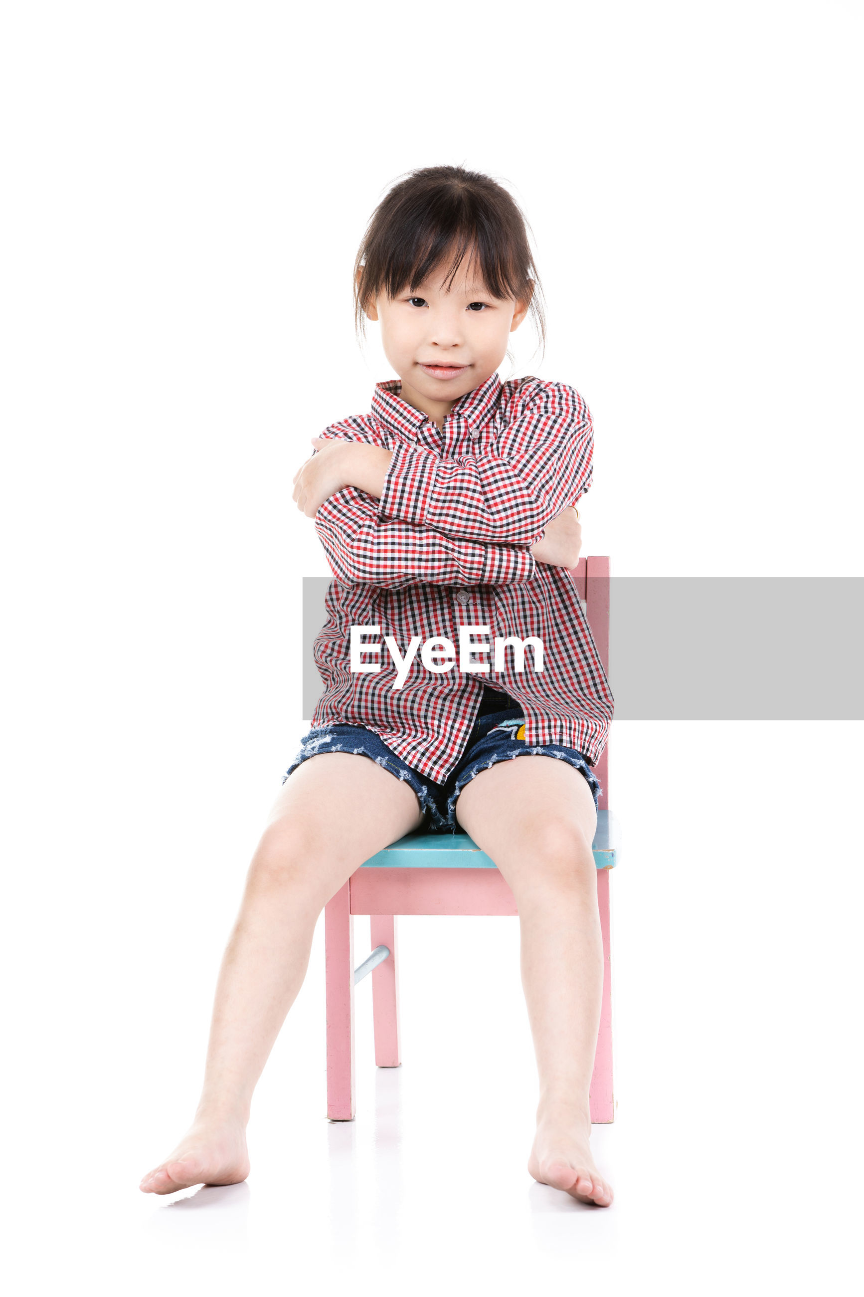 Portrait of cute girl sitting on chair over white background