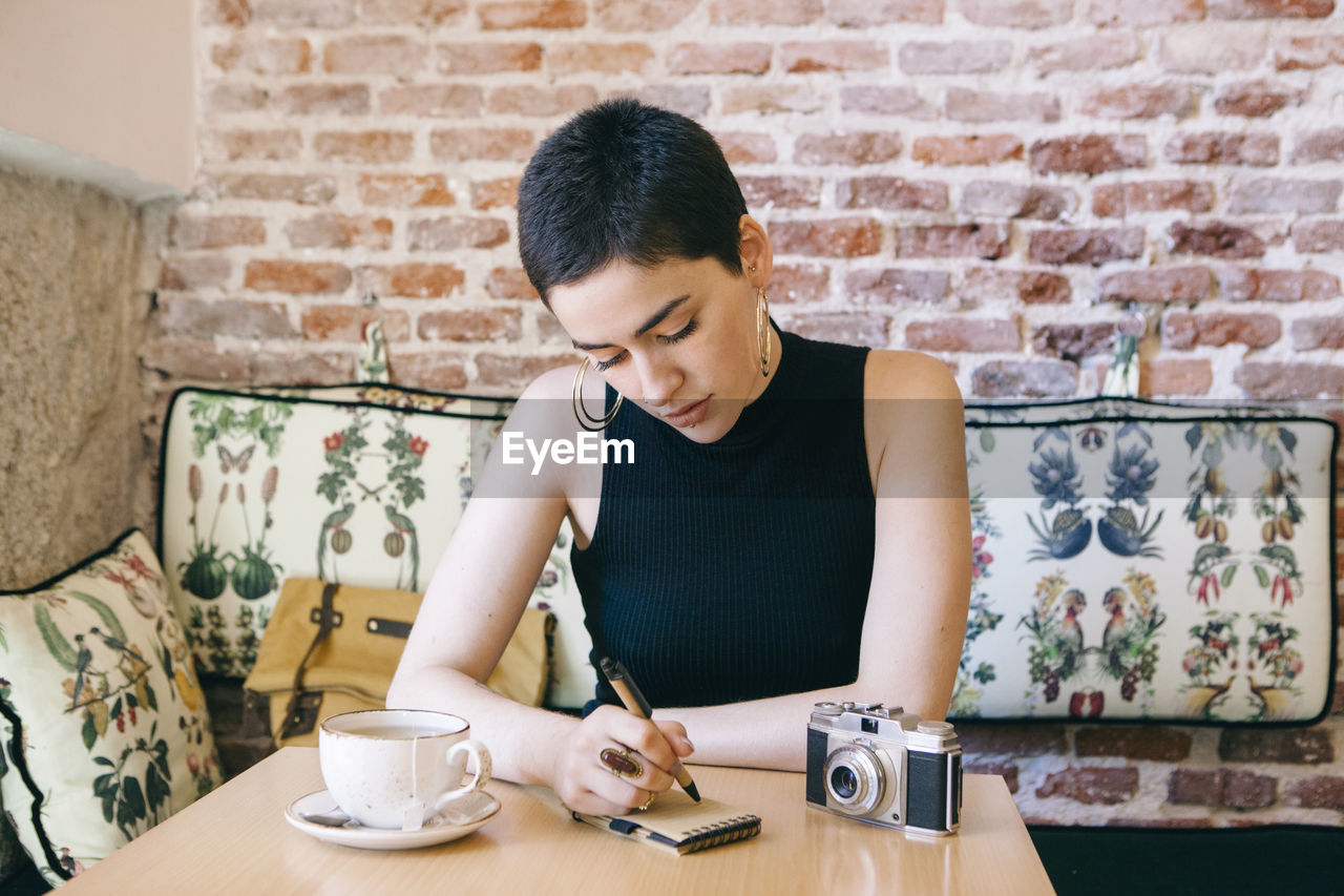 Young woman with short hair writing on note pad in cafe