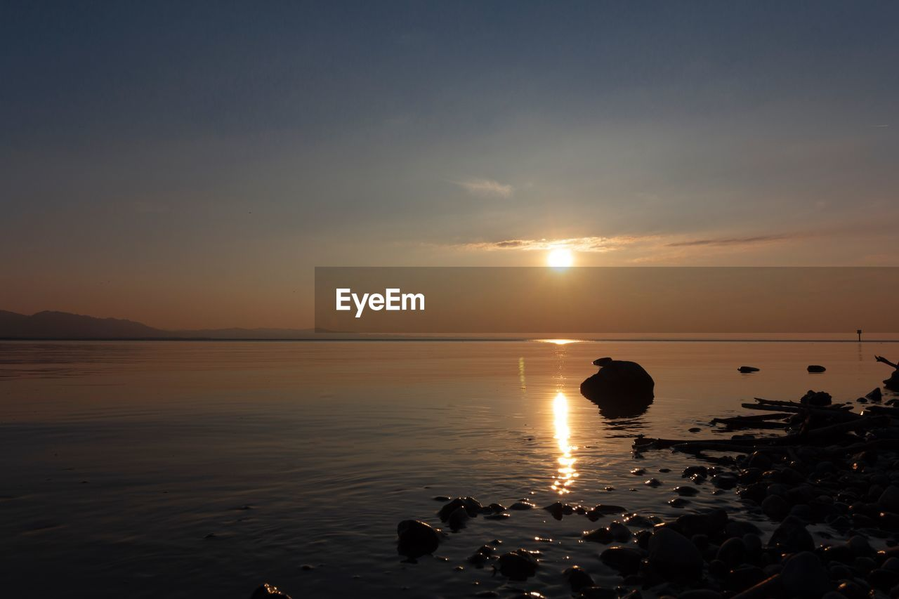 water, sky, sunset, scenics - nature, beauty in nature, sea, tranquil scene, tranquility, sun, beach, reflection, nature, idyllic, orange color, land, horizon over water, rock, cloud - sky, sunlight, no people, outdoors