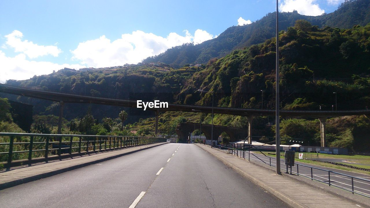 mountain, transportation, road, sky, connection, the way forward, direction, nature, day, railing, built structure, no people, beauty in nature, bridge, road marking, cloud - sky, sign, mountain range, bridge - man made structure, marking, diminishing perspective, outdoors, crash barrier