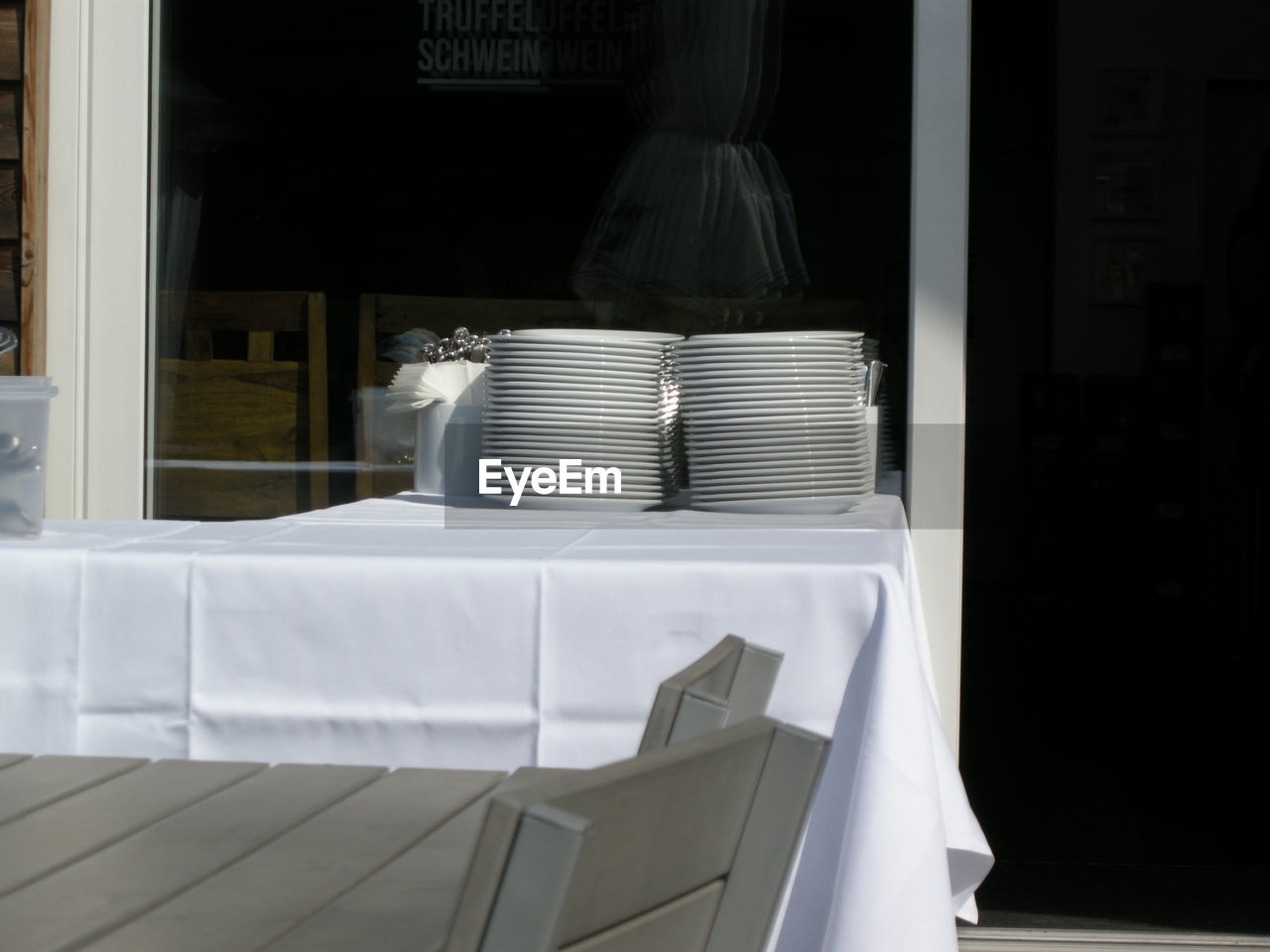 Stacked empty plates on table at outdoor restaurant