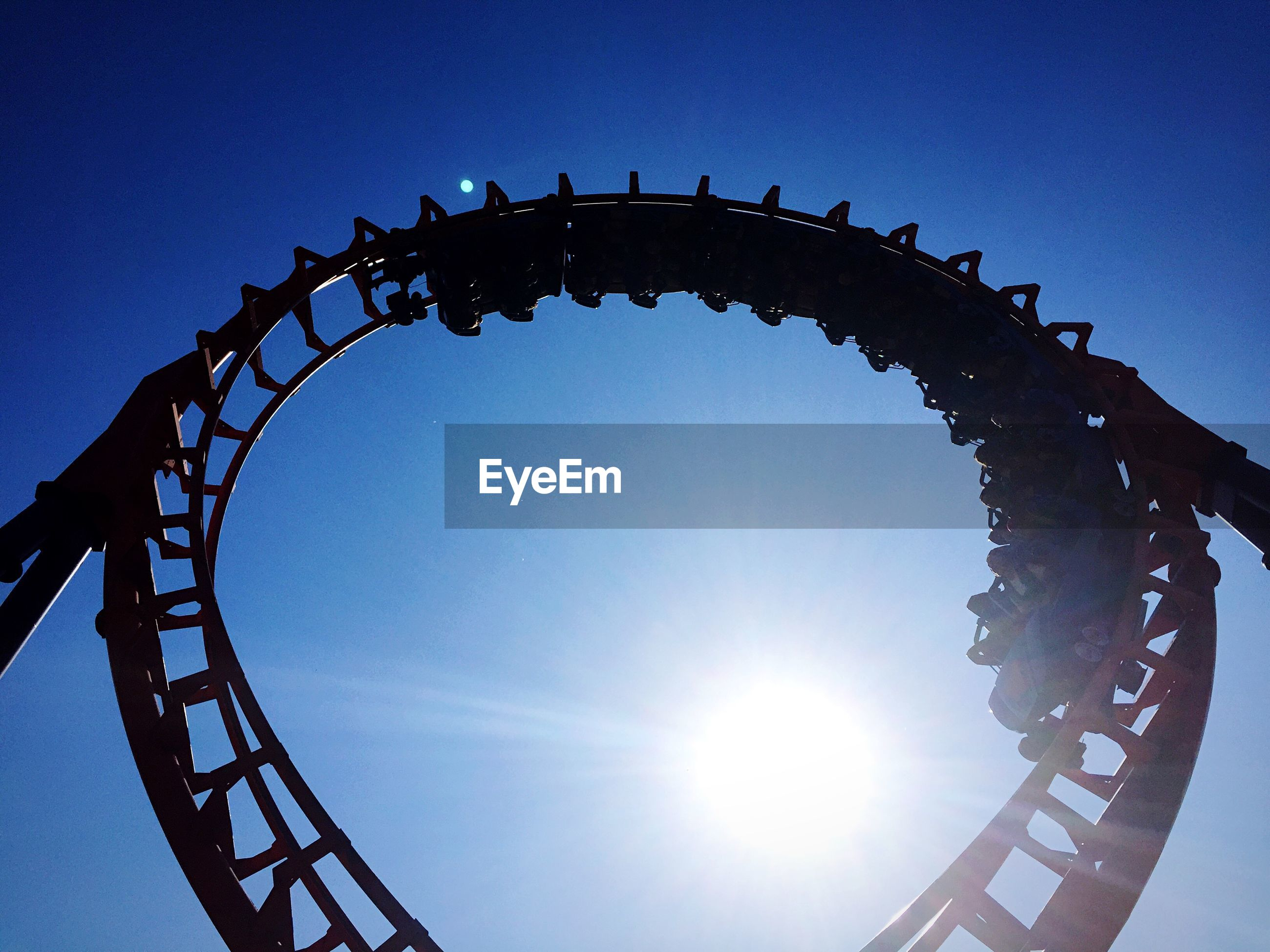 Low angle view of rollercoaster against sky on sunny day