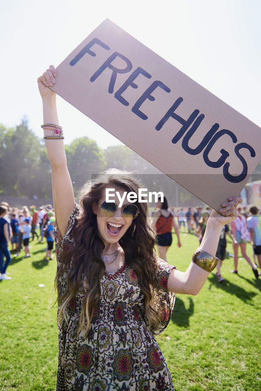 smiling, real people, happiness, communication, text, young adult, lifestyles, young women, emotion, glasses, focus on foreground, incidental people, leisure activity, western script, people, sunglasses, portrait, women, hair, hairstyle, outdoors, positive emotion, human arm, beautiful woman