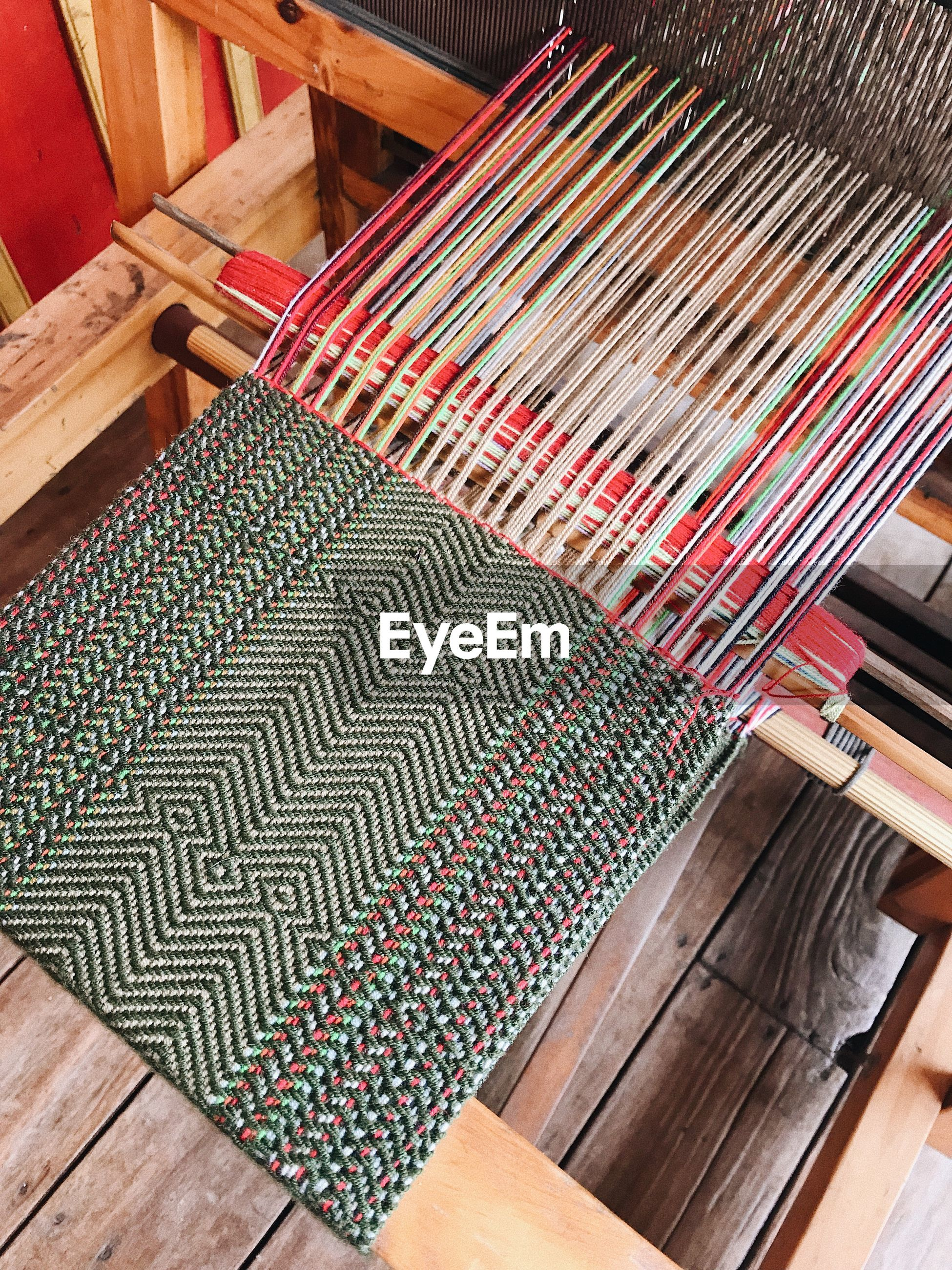 High angle view of multi colored fabric on loom in factory
