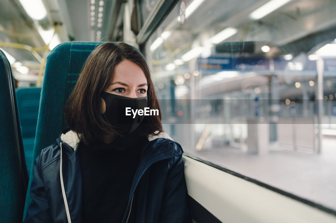 Woman in a train wearing a face mask