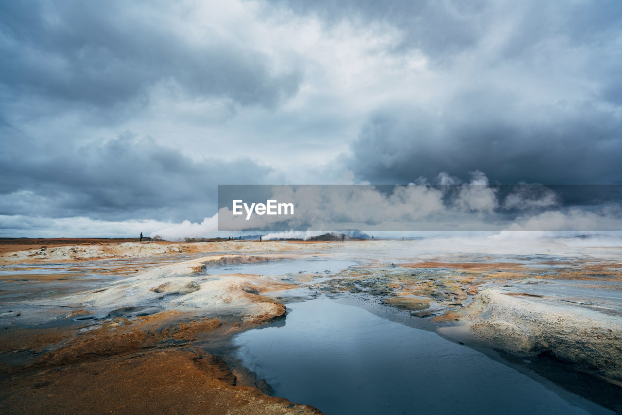 Scenic View Of Volcanic Water Against Cloudy Sky