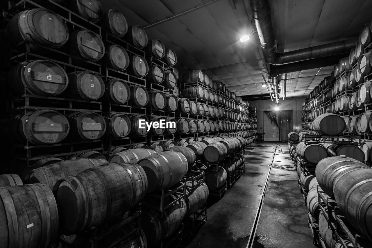 barrel, large group of objects, cylinder, in a row, cellar, food and drink, wine cellar, illuminated, indoors, refreshment, arrangement, winery, wine, winemaking, order, industry, alcohol, wine cask, business, abundance, no people, industrial equipment