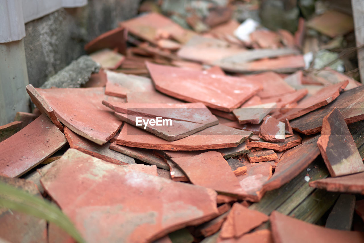 selective focus, close-up, no people, red, day, large group of objects, still life, metal, damaged, indoors, focus on foreground, high angle view, abandoned, pink color, heap, broken, stack, run-down, abundance