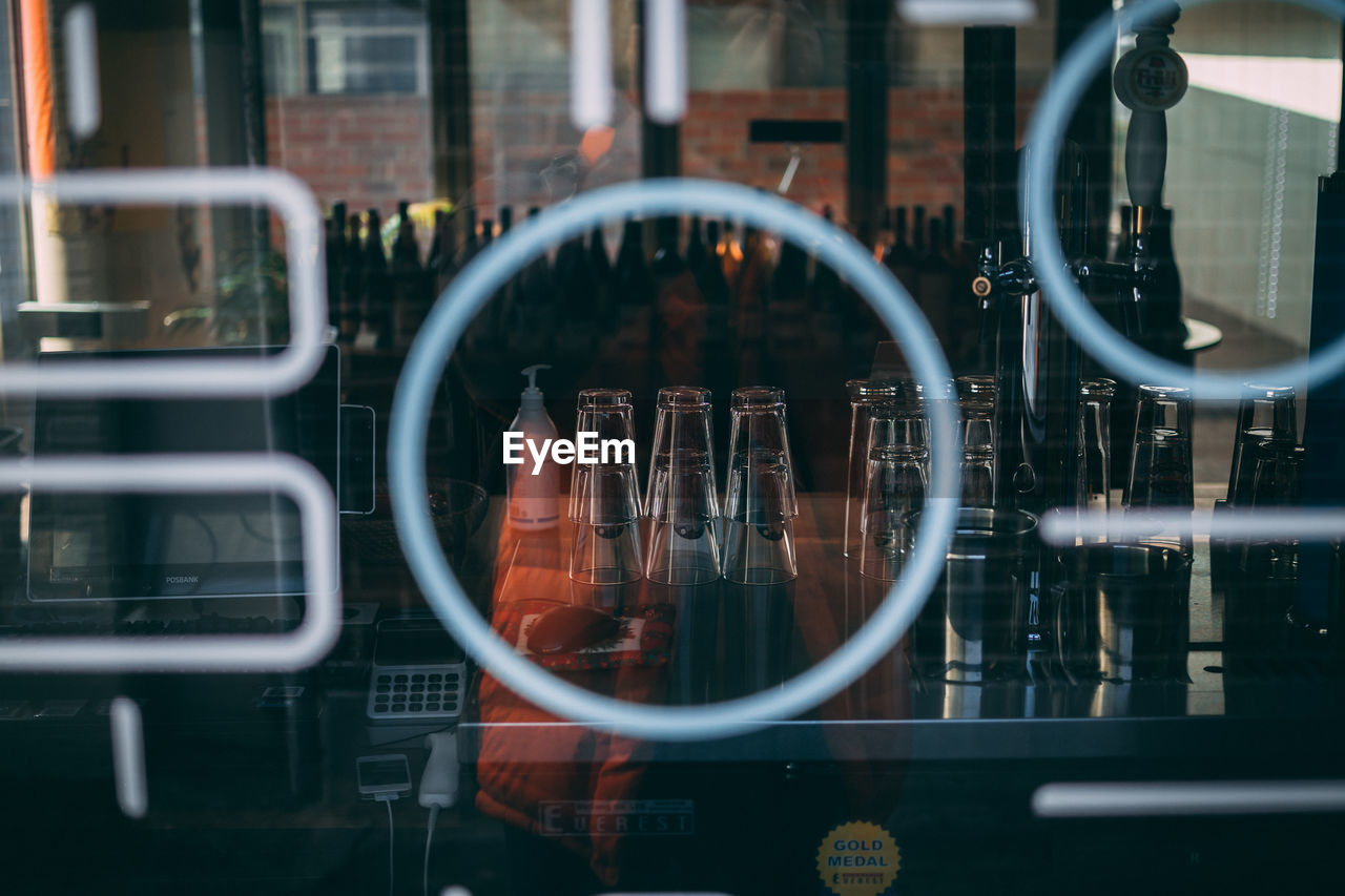 View of glasses seen through window at bar