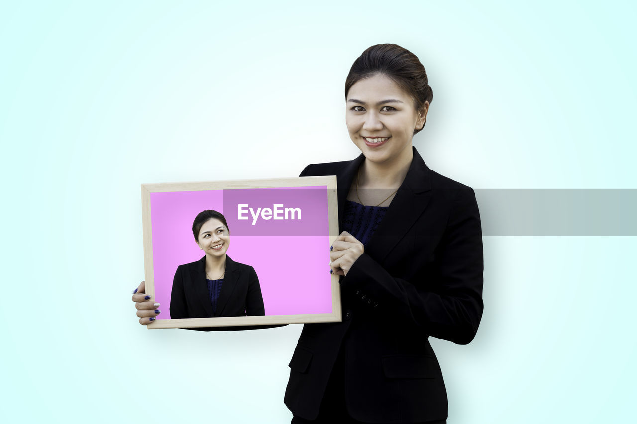 Portrait Of Smiling Businesswoman Holding Billboard While Standing Against Blue Background