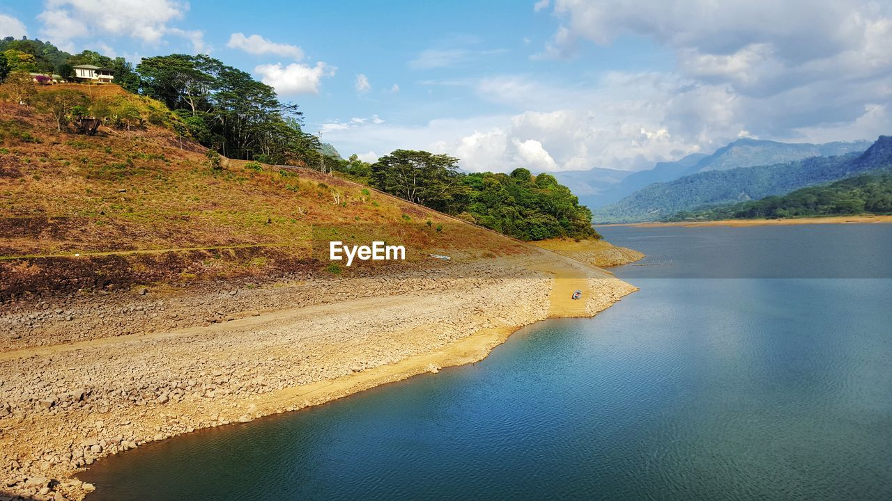 Scenic View Of River By Mountains Against Cloudy Sky On Sunny Day