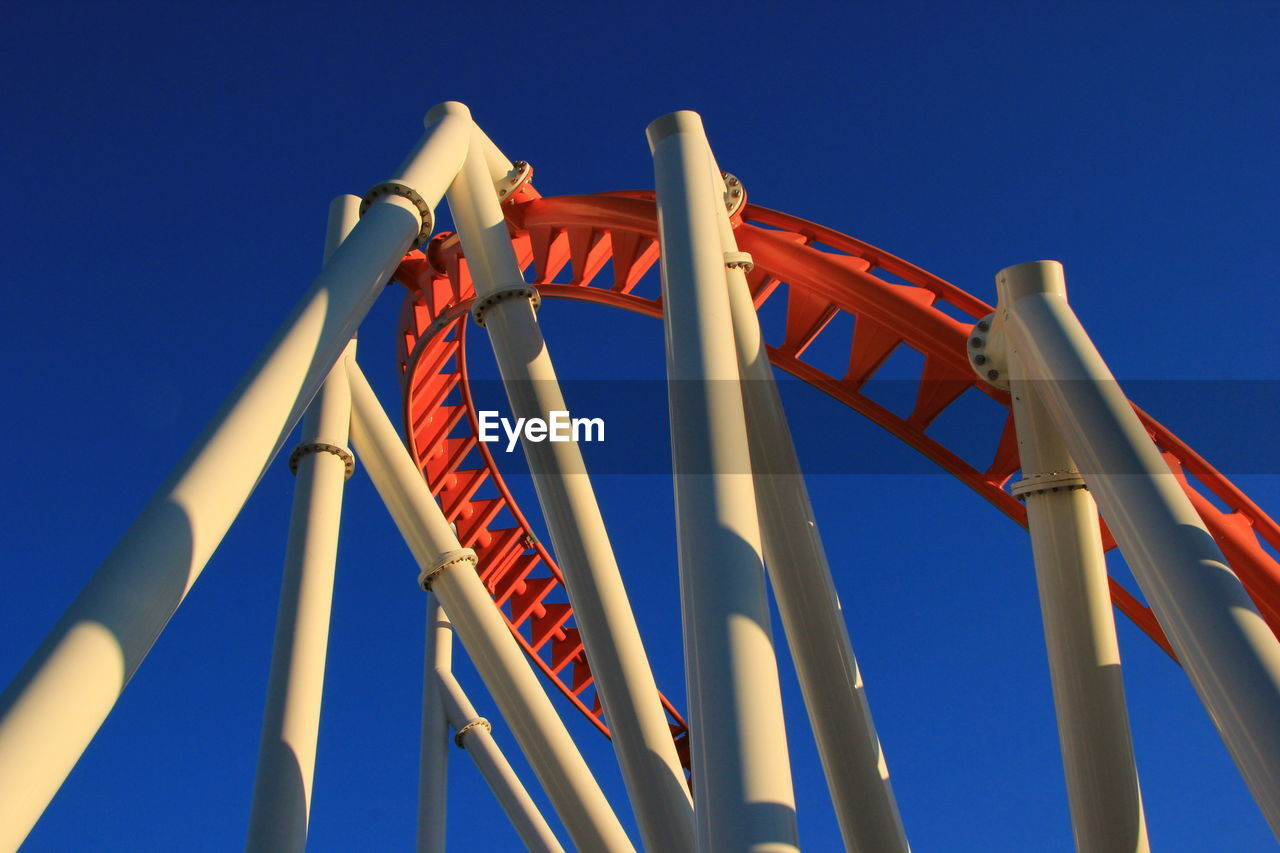 sky, blue, low angle view, clear sky, no people, arts culture and entertainment, day, nature, red, architecture, built structure, amusement park, sunlight, amusement park ride, outdoors, metal, motion, fun, rollercoaster, pattern, excitement