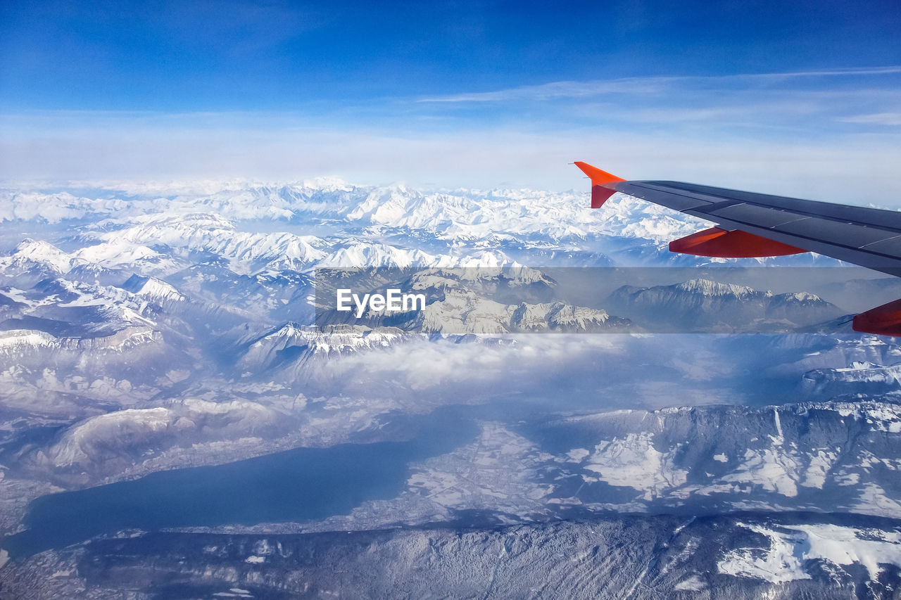 AERIAL VIEW OF CLOUDS OVER SNOW COVERED LANDSCAPE