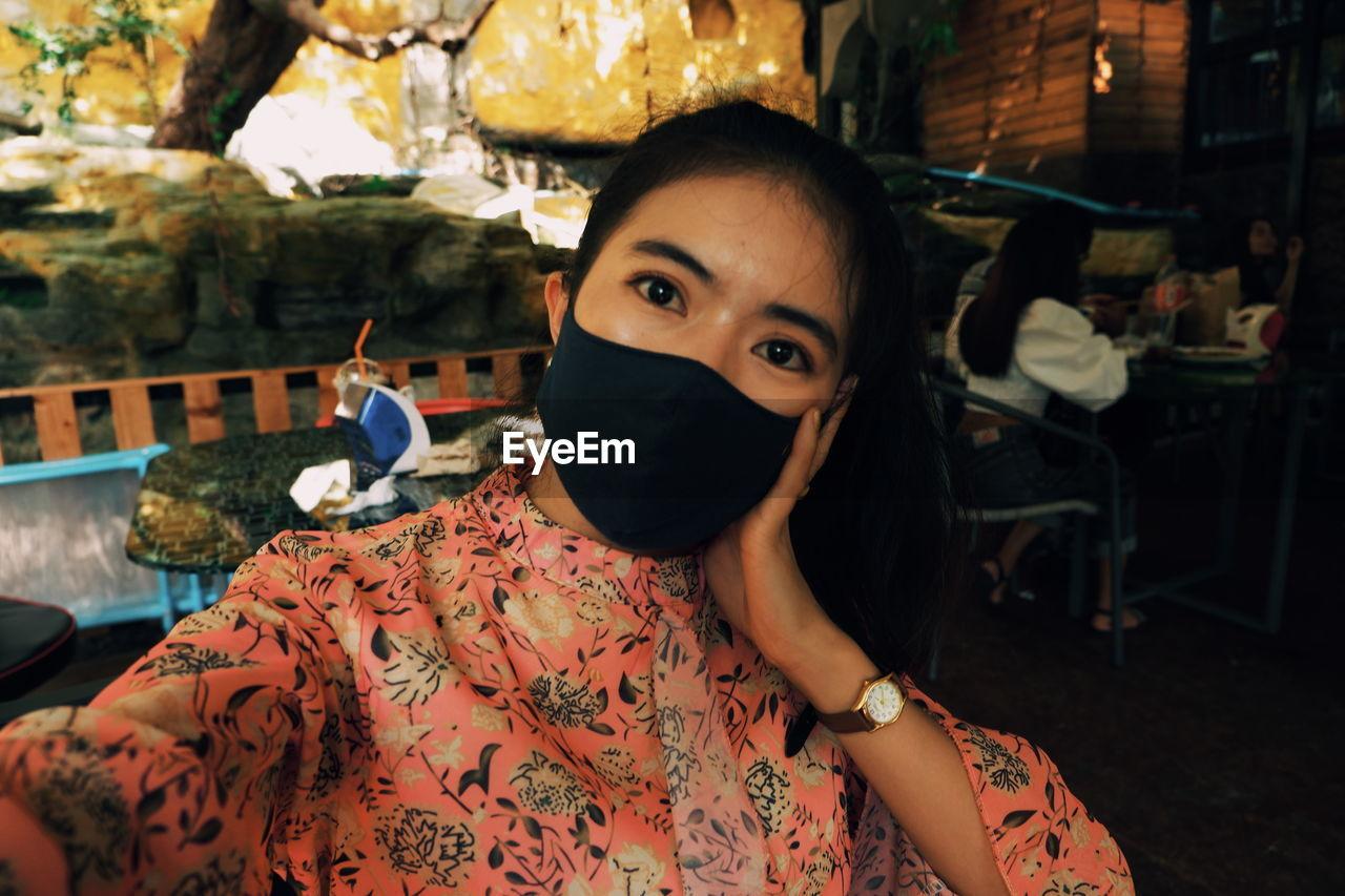 Portrait of woman wearing mask in restaurant