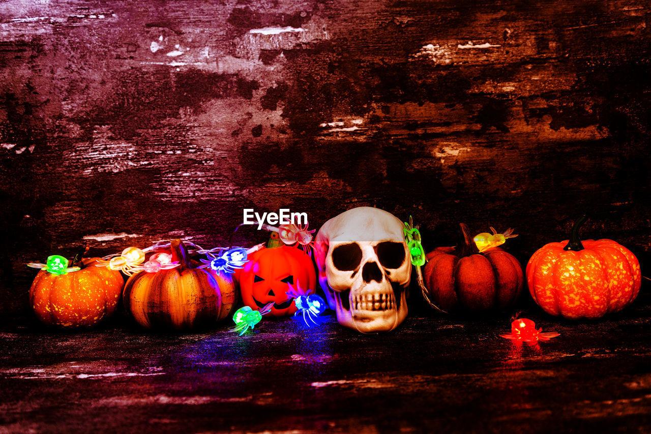 Close-up of halloween pumpkins and skull at home