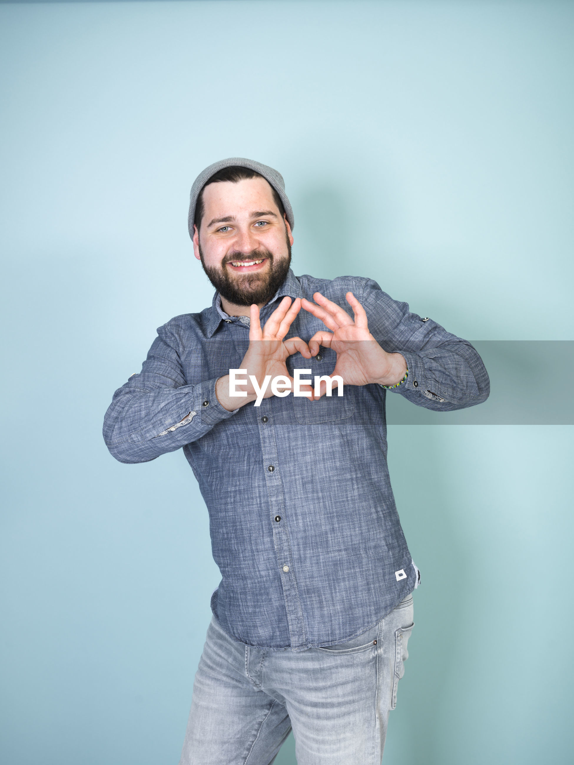 Portrait of smiling man making heart shape with hands against blue background