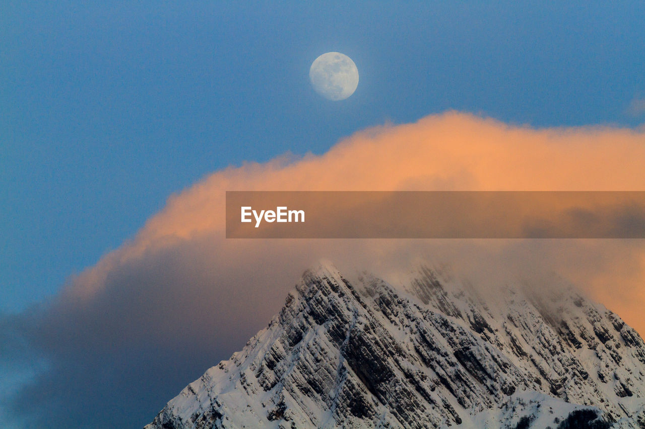 Scenic view of snowcapped mountains against clouds