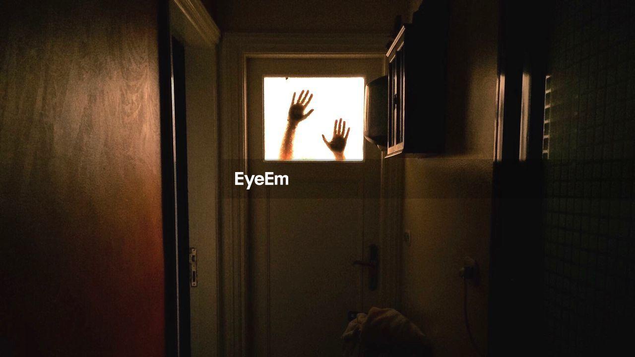 Cropped hands seen through door glass