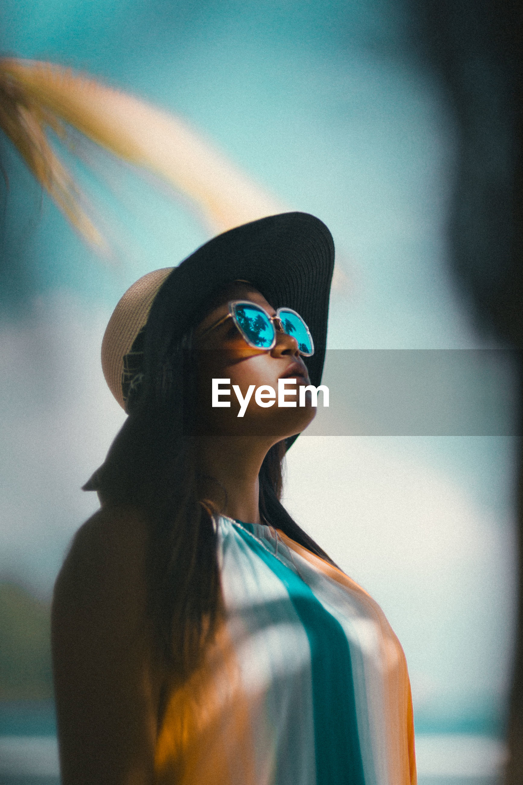 Woman wearing sunglasses and hat looking away against sky