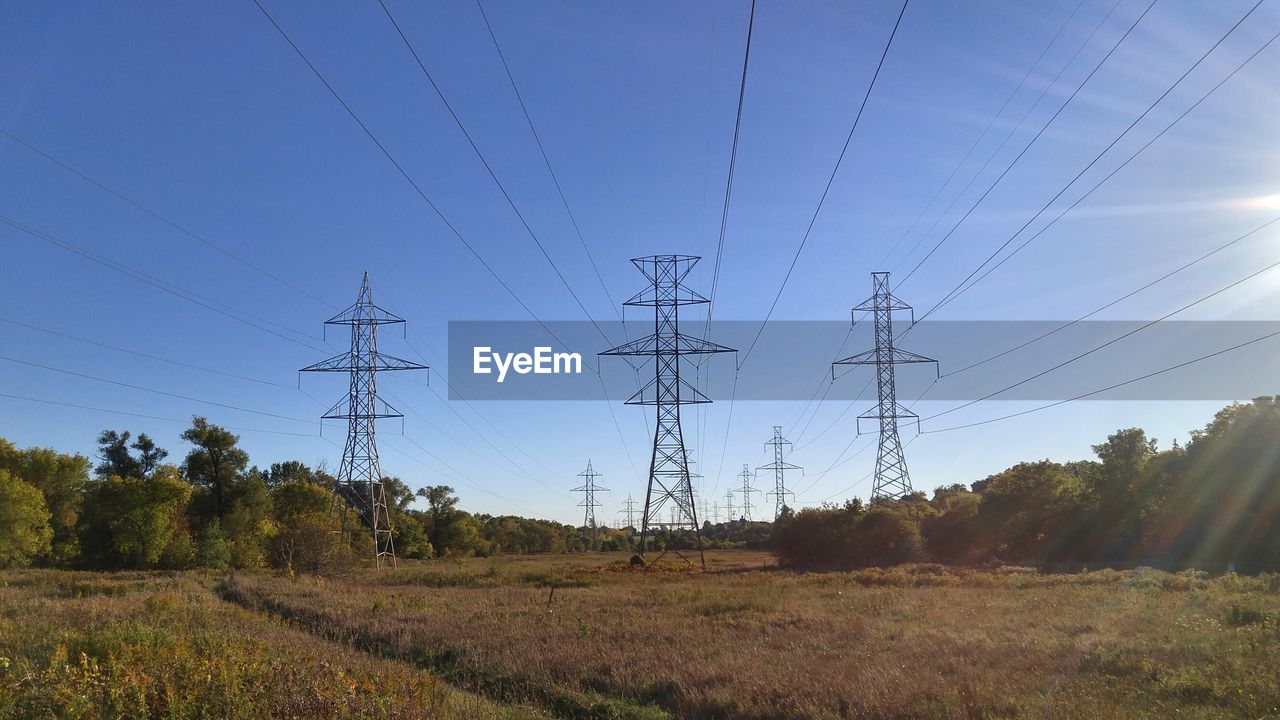 technology, power supply, electricity, cable, sky, connection, electricity pylon, power line, fuel and power generation, nature, landscape, field, land, no people, plant, tree, low angle view, environment, day, tranquility, outdoors, iron - metal, electrical equipment, complexity, electrical component