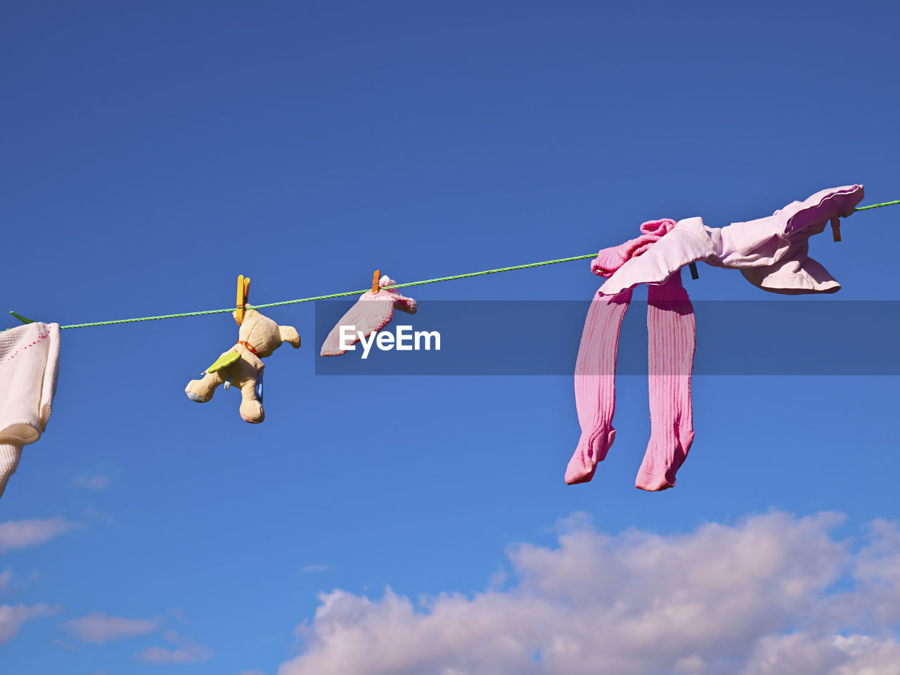 sky, hanging, low angle view, blue, clothing, nature, rope, day, clothesline, cloud - sky, clothespin, pink color, sunlight, outdoors, copy space, real people, people, laundry, side by side