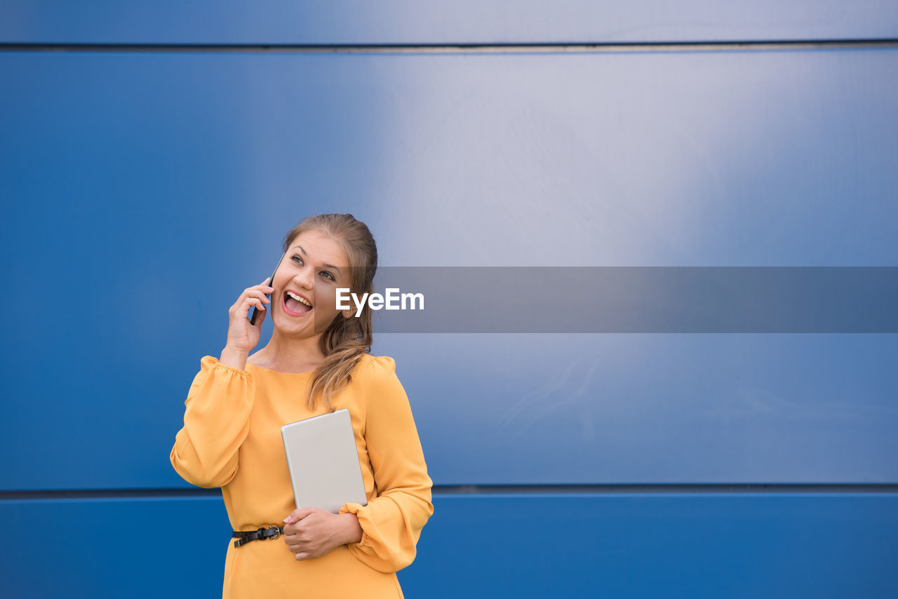 Happy Woman Talking On Mobile Phone While Standing Against Wall