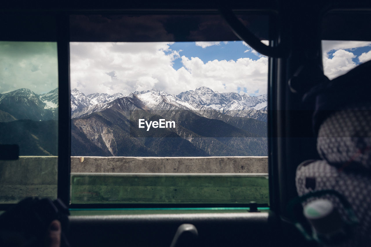 mountain, transparent, vehicle interior, window, glass - material, scenics - nature, mountain range, sky, winter, mode of transportation, environment, landscape, beauty in nature, cloud - sky, snow, travel, cold temperature, transportation, nature, snowcapped mountain, outdoors, mountain peak