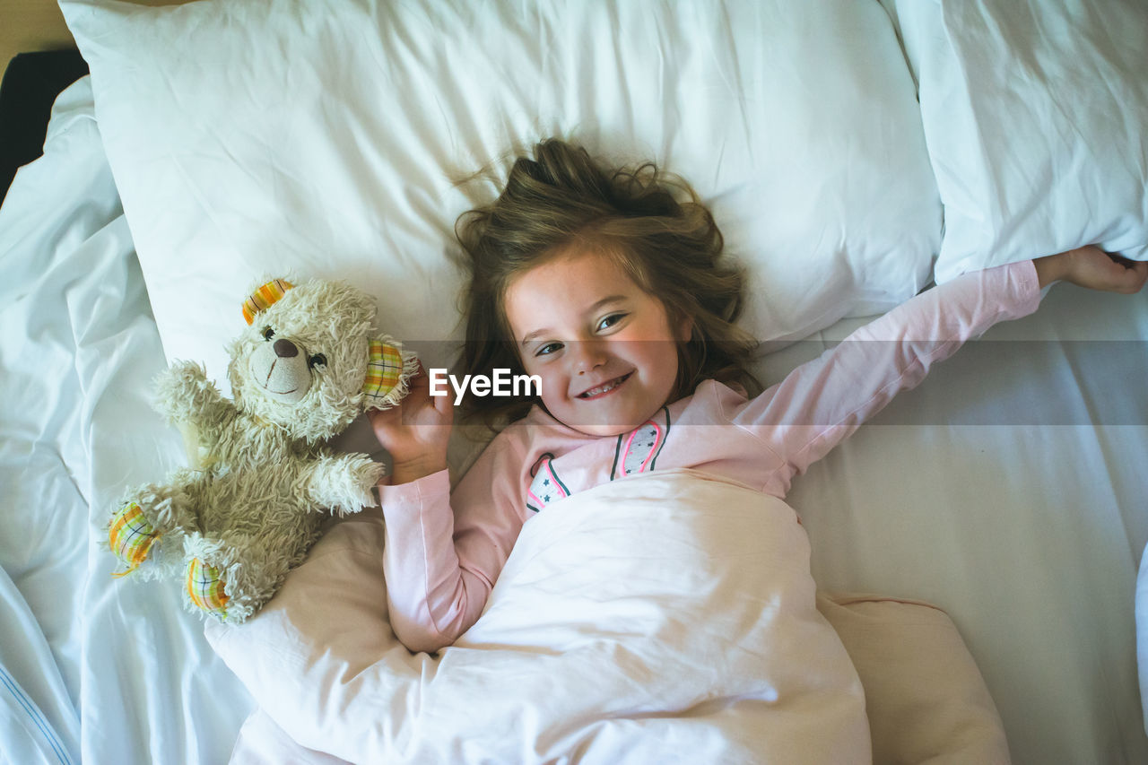 Girl lying on bed with stuffed toy at home