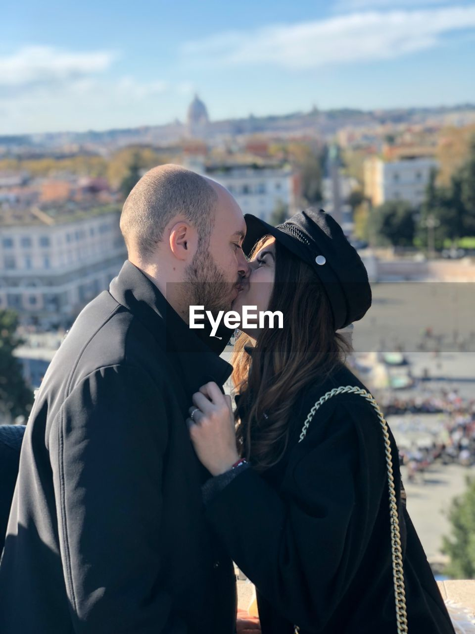 Side View Of Young Couple Kissing While Standing In City