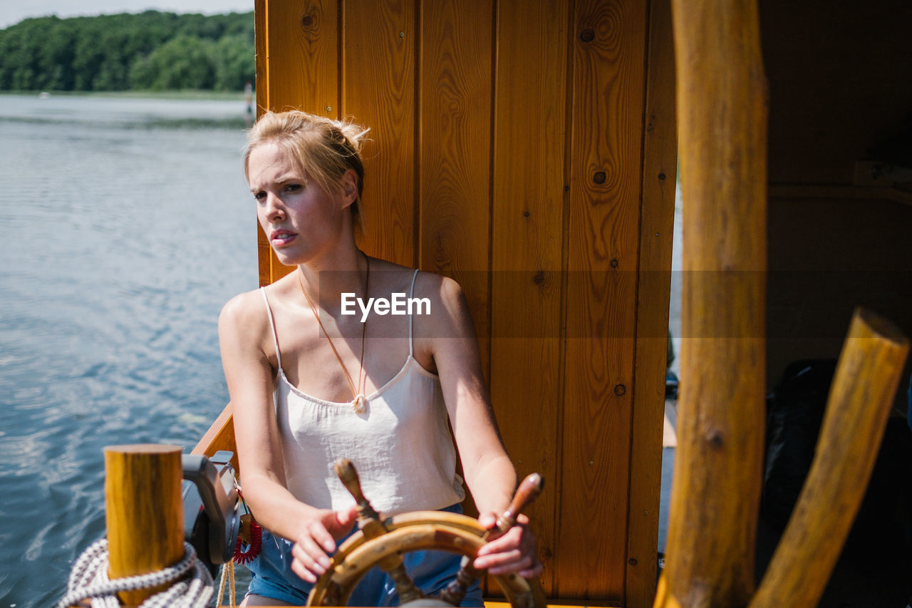 Woman Sitting By Wheel In Boat On Lake