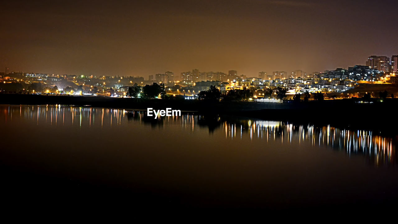 city, architecture, building exterior, water, built structure, reflection, illuminated, building, cityscape, night, sky, no people, waterfront, nature, residential district, copy space, outdoors, lake, beauty in nature