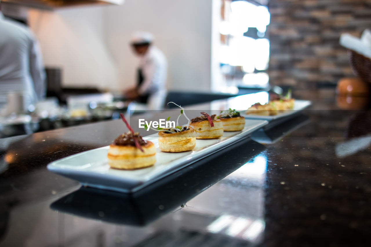 food and drink, food, freshness, indoors, selective focus, table, real people, ready-to-eat, plate, kitchen, incidental people, lifestyles, one person, business, focus on foreground, restaurant, kitchen counter, domestic room, men, tray, chef