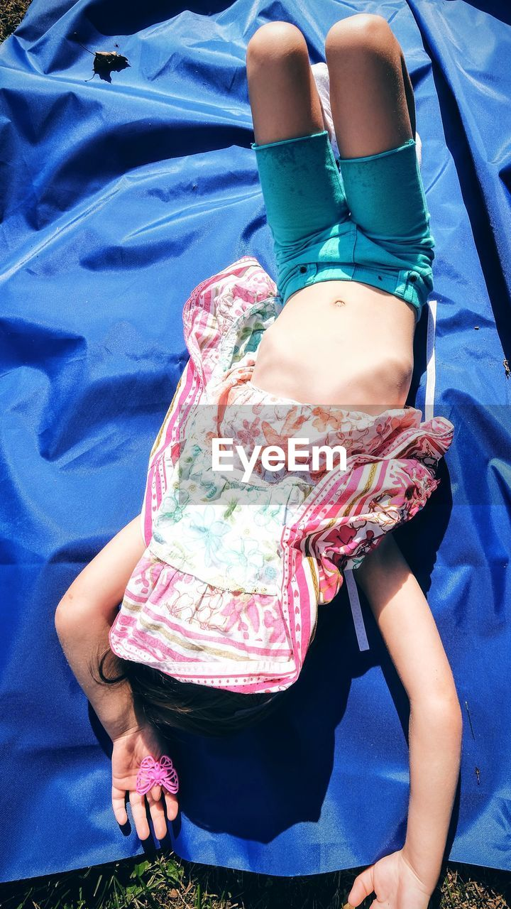 Full Length Of Girl With Covered Face Sleeping On Blue Fabric In Yard