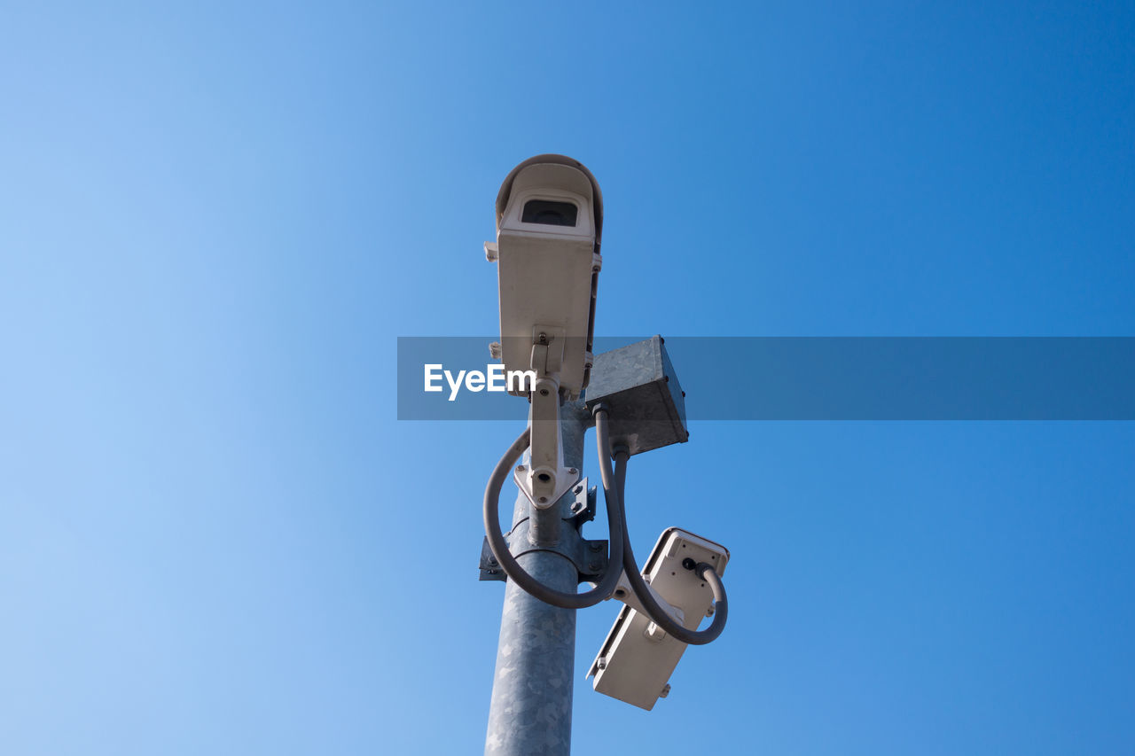 Close-Up Of Security Camera Against Clear Blue Sky