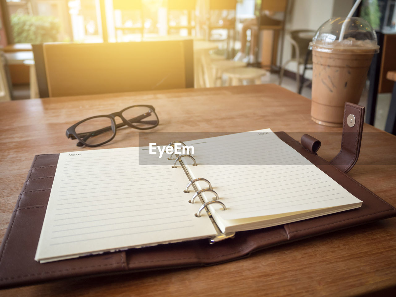table, paper, pen, drink, book, glass, publication, drinking glass, still life, indoors, no people, note pad, household equipment, refreshment, food and drink, glasses, wood - material, business, eyeglasses, education