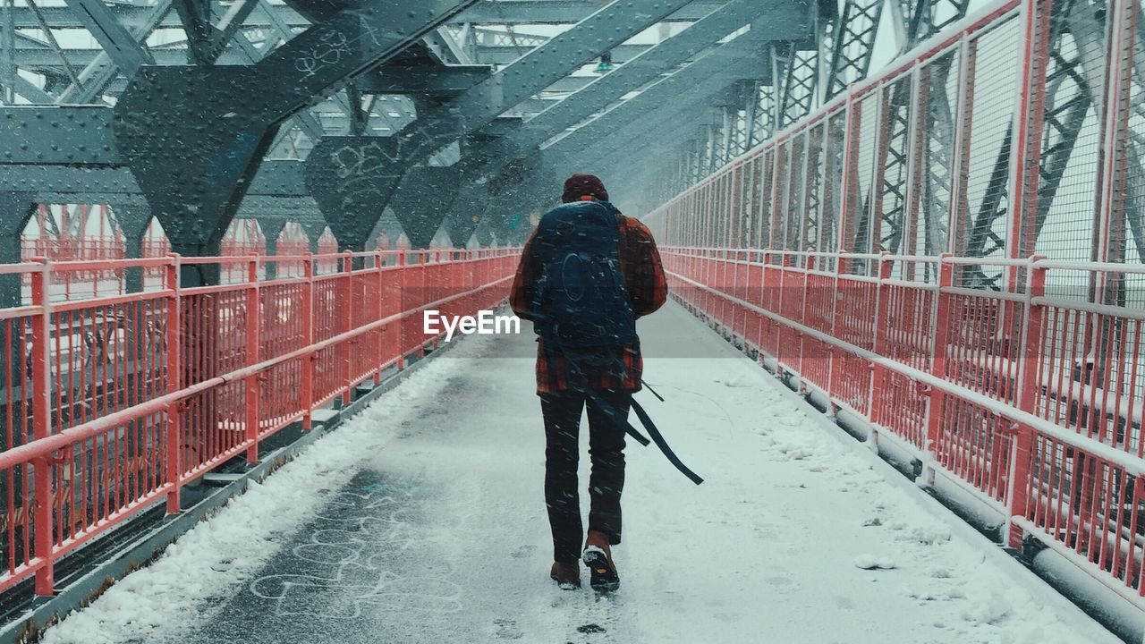 Full Length Rear View Of Man Walking On Bridge During Snowfall