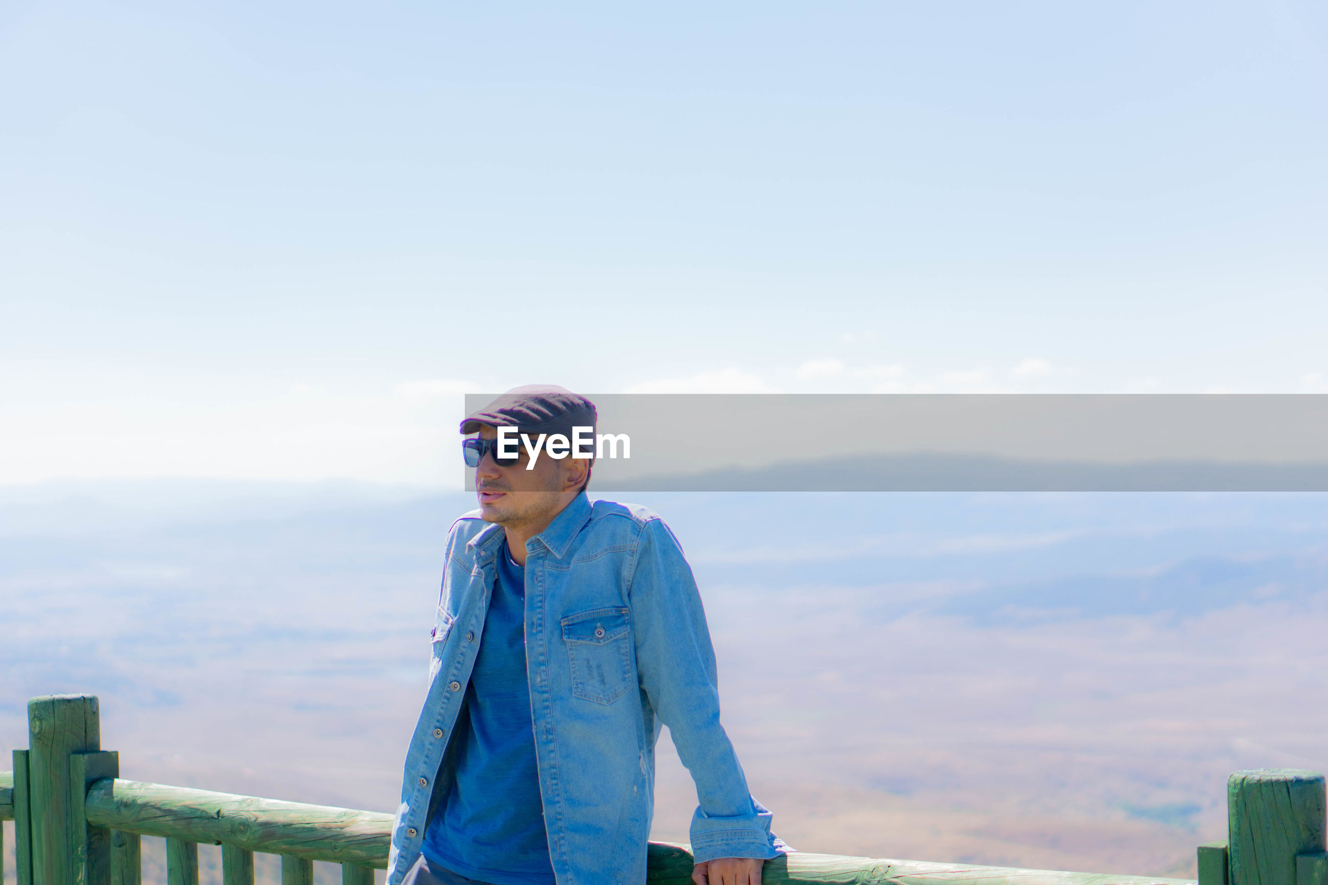 Man wearing sunglasses while standing against sky